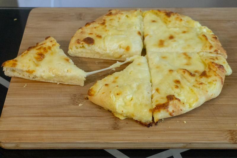 Cutting into your cheesy Megruli Khachapuri